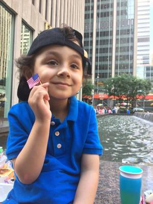 Reuben holds up a small American flag as he poses for a photo in New York
