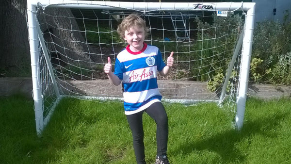 Jess is wearing a QPR shirt, standing in front of a goal in a garden with her foot on a football
