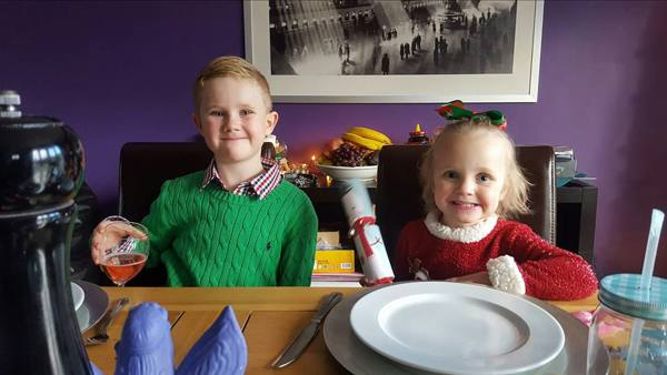 brother and sister sitting at table on christmas day