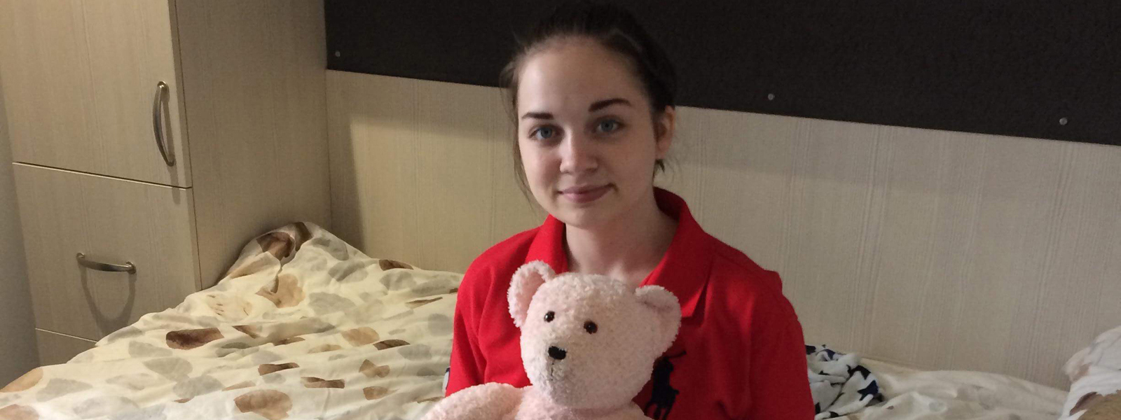 Charlotte sits on her bed at University holding a teddy bear