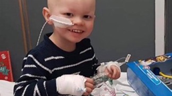 Little boy sat on hospital bed playing with Lego