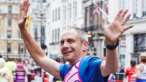 Man waves with both hands as hes running a marathon