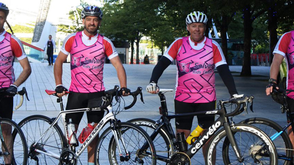 Four cyclists post for a photo holding their bikes and wearing Solving Kids Cancer jerseys